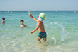 Happy smiling little boy run play with waves on beach. Italy. Summer