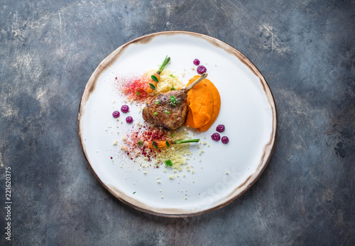 Fototapeta Duck leg confit with batat puree, carrots and couscous, restaurant meal obraz