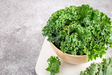 Bowl Of Curly Green Kale On Gr...