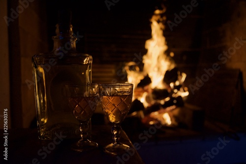 Two glass mugs of hot drink or alcoholic drink in front of warm fireplace. Magical relaxed cozy atmosphere near fire. Autumn or winter concept