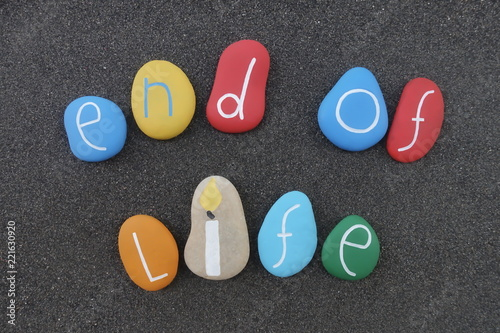 Fotografía  End of life phrase with a composition of colored stones over black volcanic sand