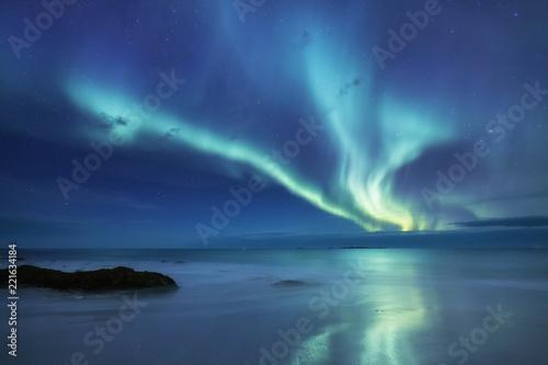 Foto auf Gartenposter Nordlicht Aurora borealis on the Lofoten islands, Norway. Green northern lights above ocean. Night sky with polar lights. Night winter landscape with aurora and reflection on the water surface.