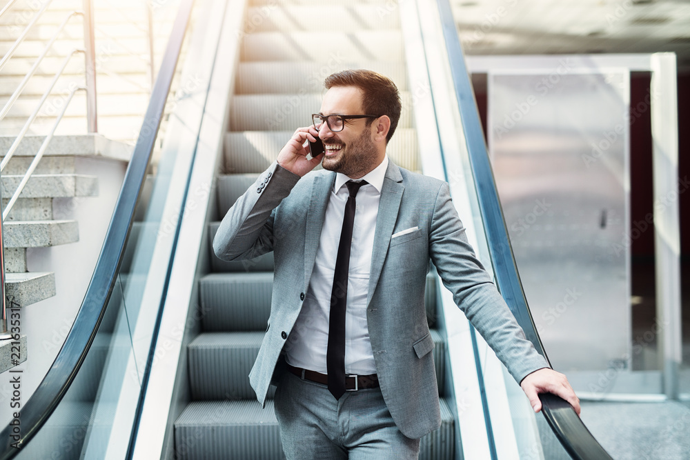 Fototapeta Young modern successful businessman talking on the telephone while standing on a escalator. Smiling about good business offer.