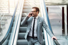 Young Modern Successful Businessman Talking On The Telephone While Standing On A Escalator. Smiling About Good Business Offer.