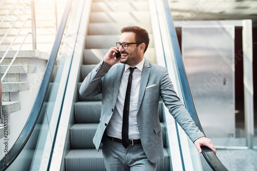 Fotomural Young modern successful businessman talking on the telephone while standing on a escalator