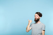Leinwanddruck Bild smiling man pointing behind his back to a virtual object or text. copy space for advertisement or product placement. portrait of a bearded hipster guy on blue background.