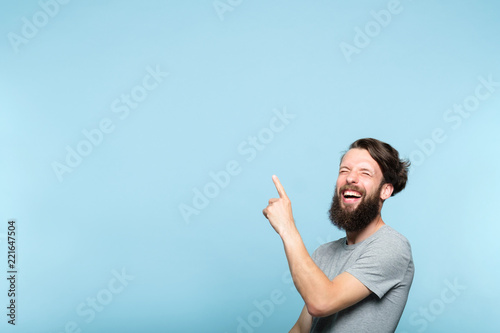 laughing man pointing behind sideways to a virtual object or text Fototapeta