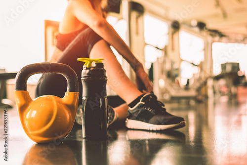 Stampa su Tela Close up kettlebells with woman exercise workout in gym fitness breaking relax after sport training with protein shake bottle background