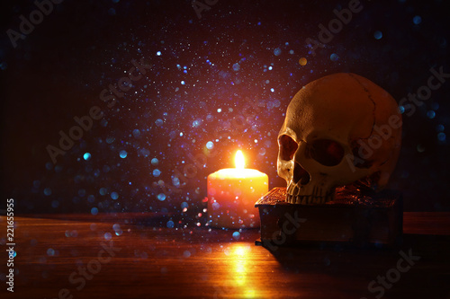 Photo Human skull, old book and burning candle over old wooden table and darl background