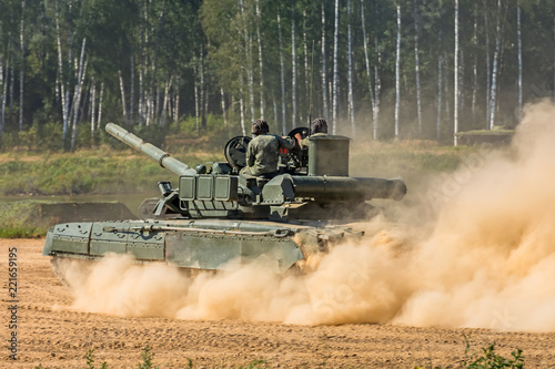 Photo  Heavy armor tank with dust from under the caterpillars in the field of battle