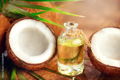 Coconut oil in a bottle with coconuts and green palm tree leaf. Healthy eating. Skincare concept