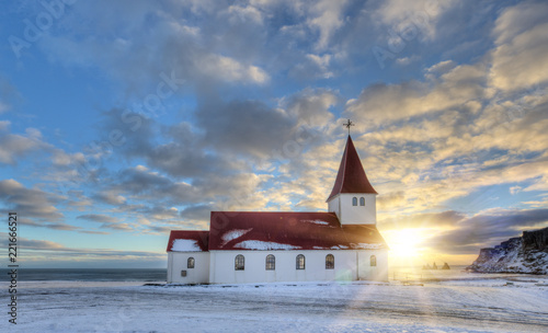 Typical red colored wooden church in Vik town, Iceland in winter.