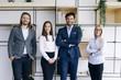 Group of friendly businesspeople in suits standing at office