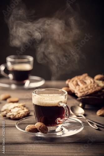 Steaming coffee cup on old wooden background with copy space. Retro style toned dark photography.