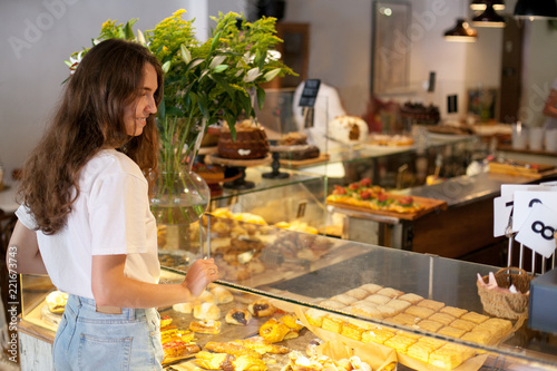 In de dag Bakkerij Young brunette smile woman near modern display of bakery with different kinds of cookie and buns and choose and make order.