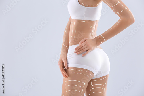 Obraz Young woman with beautiful slim body on light background - fototapety do salonu