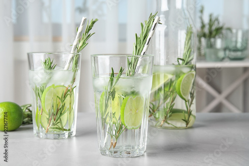 Tasty refreshing cocktail with rosemary and lime on table