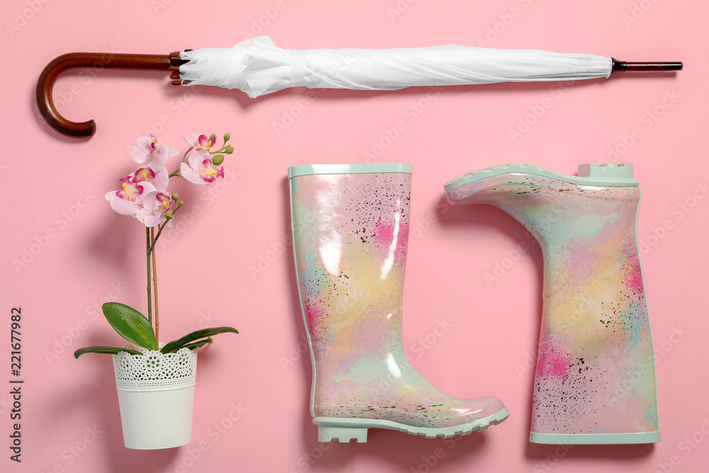 Flat lay composition with umbrella and rubber boots on color background