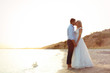 Wedding couple holding hands and kissing on beach. Space for text