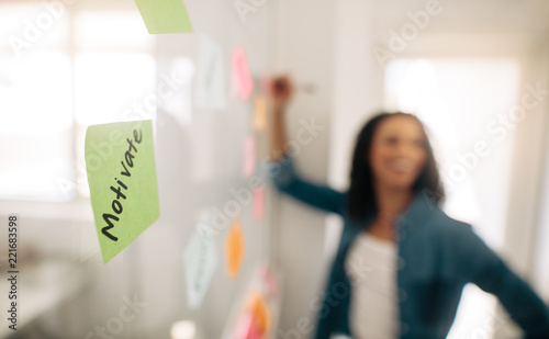 Fotografía  Sticky note with motivate written on it pasted on glass wall