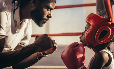 Fototapeta Boxing trainer teaching a kid about boxing