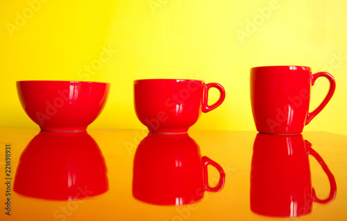 three red cup mug bowl kitchen wear on colorful yellow background