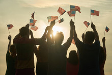 Group Of People Waving American Flags. Silhouette Of People With Usa Flags Against Evening Sunny Sky Background.