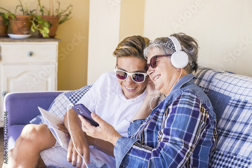 Fotografie, Obraz  couple young and old grandmother and teenager nephew family time together listen music with earphones and enjoy the day