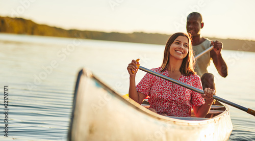 Canvas-taulu Laughing woman having a fun day canoeing with her boyfriend
