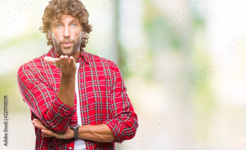 Valokuvatapetti Handsome hispanic model man over isolated background looking at the camera blowing a kiss with hand on air being lovely and sexy
