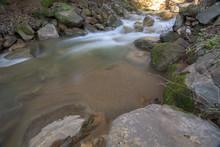 River Flowing Between Rocks