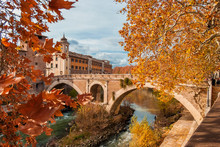 Autumn And Foliage In Rome. Red And Yellow Leaves Near Tiber Island With Ancient Roman Bridge, In The City Historic Center