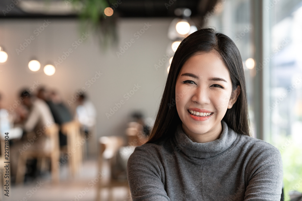 Fototapeta Portrait of young attractive asian woman looking at camera smiling with confident and positive lifestyle concept at cafe background. Headshot of natural makeup of young girl, asia student or teen.