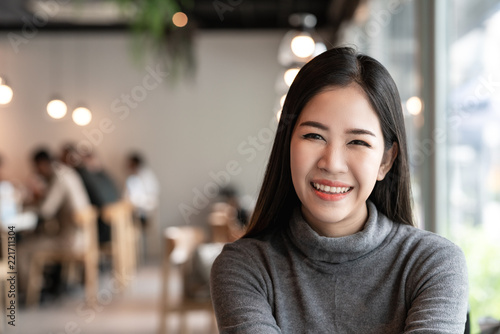 Fototapeta Portrait of young attractive asian woman looking at camera smiling with confident and positive lifestyle concept at cafe background. Headshot of natural makeup of young girl, asia student or teen. obraz