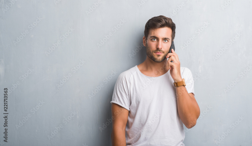 Fototapety, obrazy: Handsome young man over grey grunge wall speaking on the phone with a confident expression on smart face thinking serious