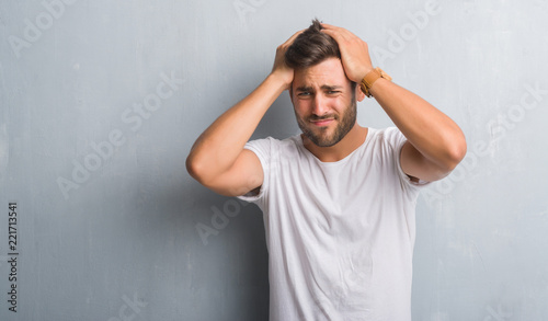 Handsome young man over grey grunge wall suffering from headache desperate and stressed because pain and migraine Canvas-taulu