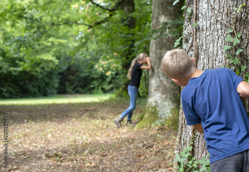 Fotomural  Kids playing hide and seek in the forrest