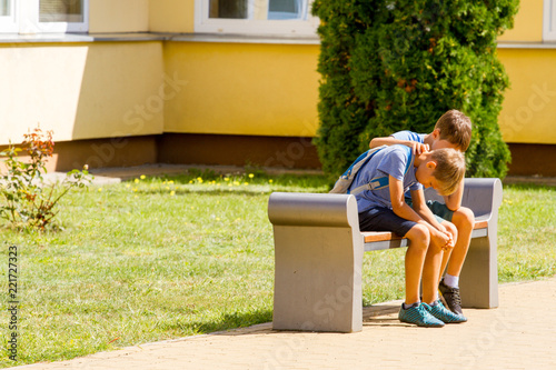 Kid comforting consoling upset sad boy in school yard Canvas Print