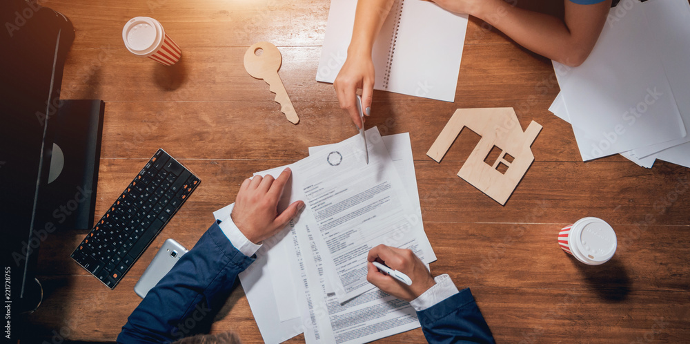 Fototapeta Man sign a home insurance policy on home loans. Estate agent with customer before contract signature.