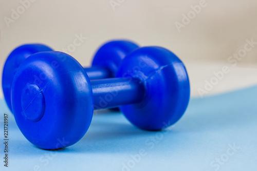 Fotografia  Bright blue dumbbells on a blue background