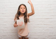 Young hispanic kid over white brick wall giving mother day card annoyed and frustrated shouting with anger, crazy and yelling with raised hand, anger concept