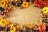 Fototapeta Kwiaty - Jesienne tło na tkaninie z juty, wokół liście, śliwki, żółte kwiaty, kasztany, orzechy i jarzębina
