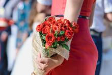 Red Wedding Bouquet Of Roses In Hands On A Background Of Red Silhouette