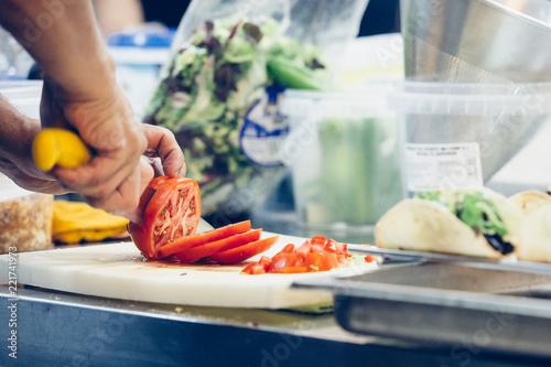 Chef hands cutting tomato