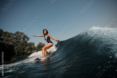 Sexy slim brunette woman wakesurfing on board down the blue water Canvas Print