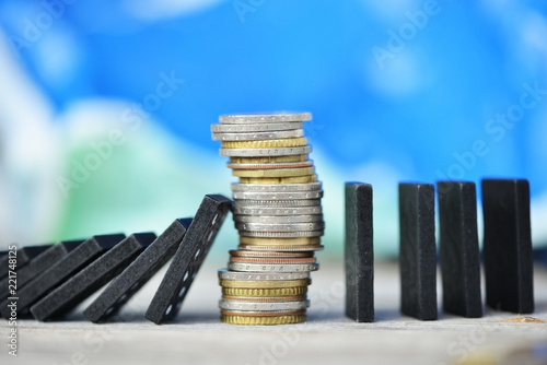 Fototapeta Strong currency or economy concept with pile of coins stopping the fall of black domino blocks  obraz
