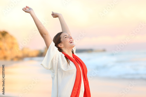 Fotografia  Excited woman celebrating sunset raising arms