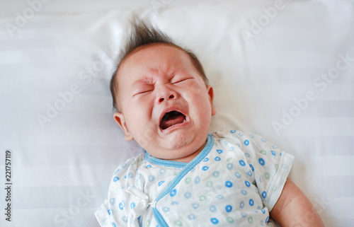 Photographie Portrait of infant baby boy crying and screaming lying on bed.