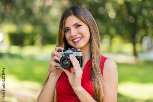 Fotografering  Smiling young woman holding a camera