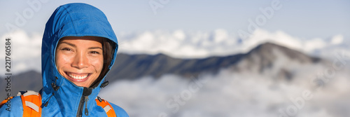 Hiking hiker woman portrait in mountain summit snow capped peaks in sunrise above clouds panoramic banner. Asian girl smiling trekking in mountains.